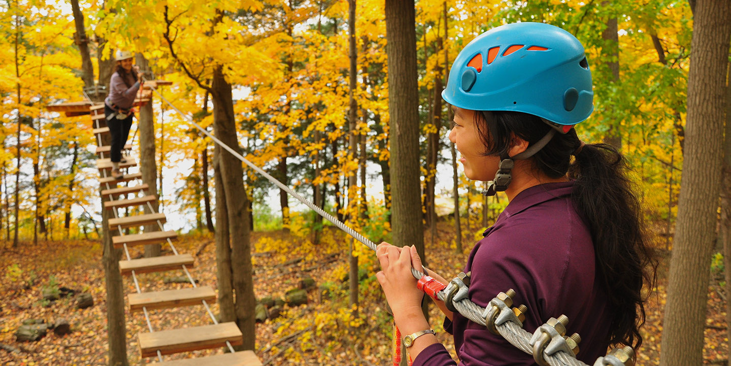young women treetop trekking at bruce's mill conservation area in the fall