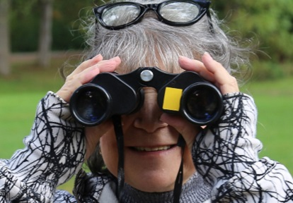 senior woman bird watching with binoculars