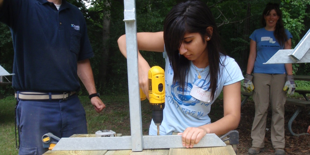 Conservation Youth Corps participant uses power tools to build a table