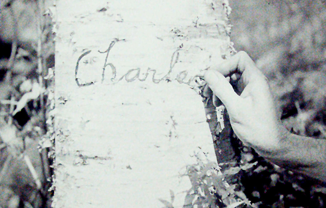 archival photograph of Charles Sauriol carving his name into a tree trunk