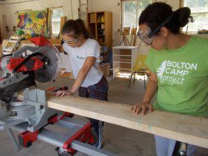 Two women sawing plank of wood