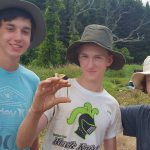 Boyd Archaeological Field School students display fishing hook unearthed at Sebastien Site