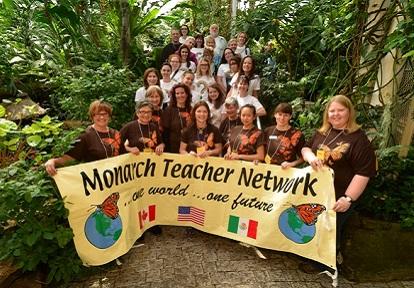 teachers pose with Monarch Teacher Network banner