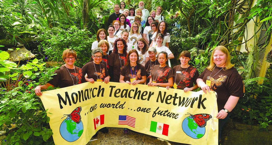 Monarch Teacher Network volunteers hold banner