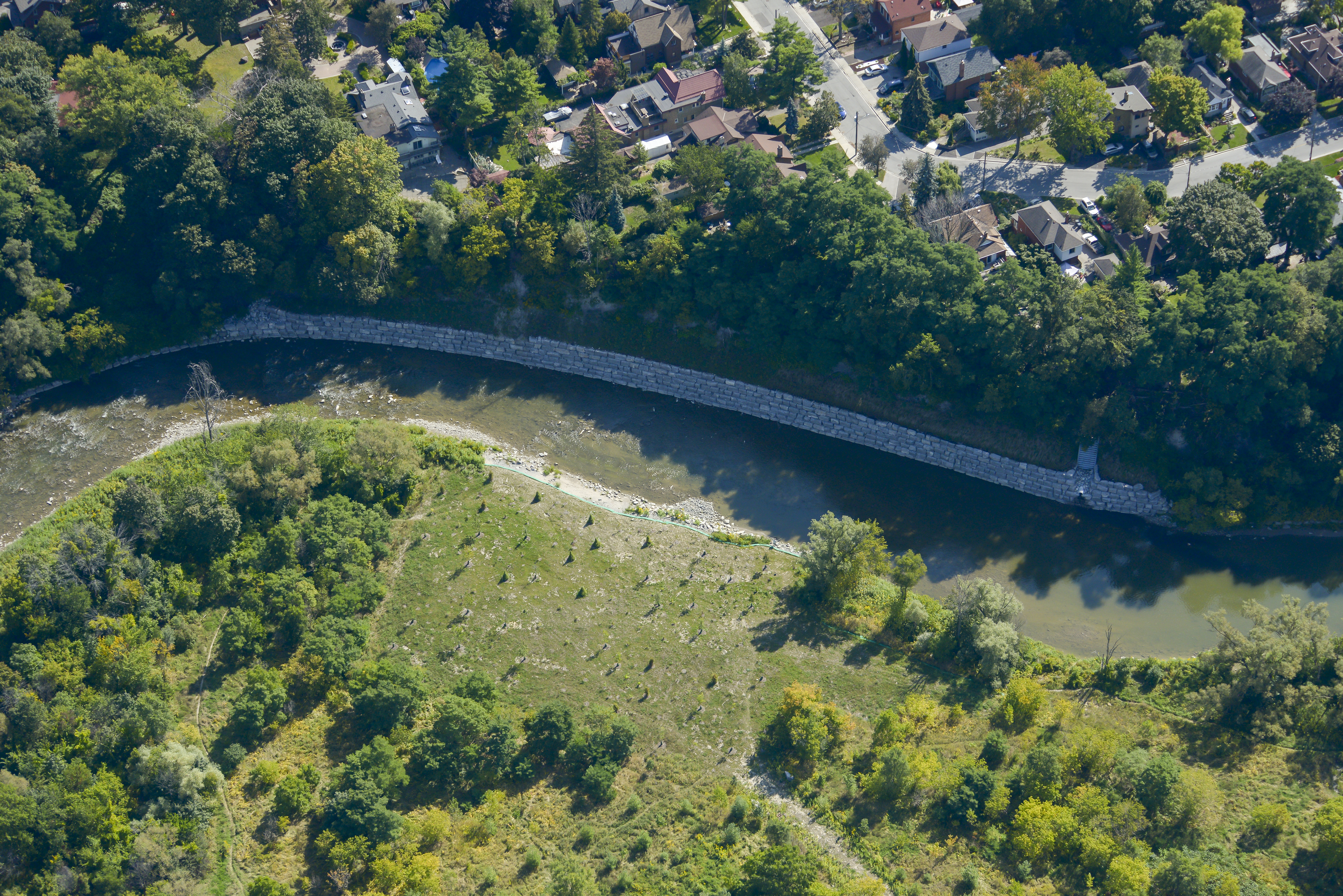 An aerial view of an armourstone wall along the bank of the Humber River
